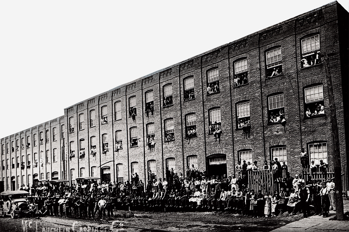 McLaughlin employees stand in front of a factory building in 1908 with some of the company's new automobiles